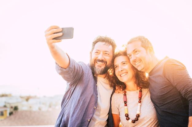 Jasnożółta grupa filtrów kaukaskich 40-letnich mężczyzn i kobiet robiących zdjęcie selfie za pomocą inteligentnego urządzenia telefonicznego