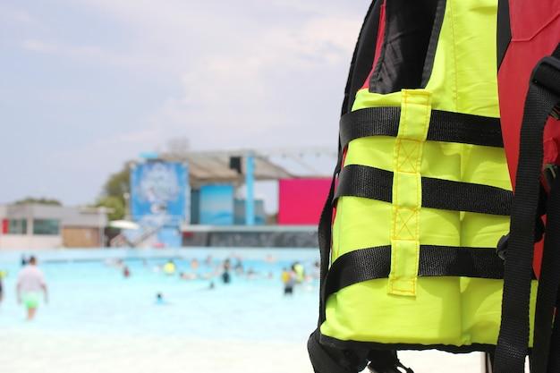 Jasnożółta kamizelka ratunkowa wisi przy basenie w parku wodnym