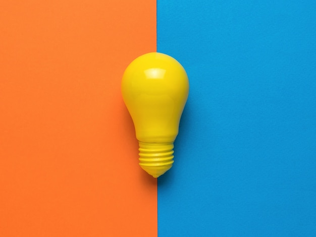 Jasnożółta żarówka na pomarańczowym i niebieskim tle. minimalizm. leżał płasko.