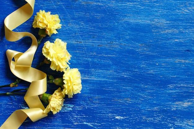 Jasnożółte goździki z żółtą jedwabną wstążką na niebieskiej powierzchni