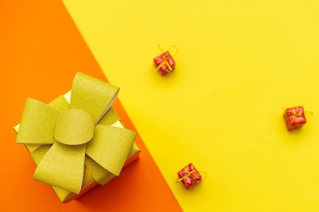 Jasnożółte pudełko ze złotą kokardą i wstążką na żółtym i pomarańczowym tle płaskie świecz...