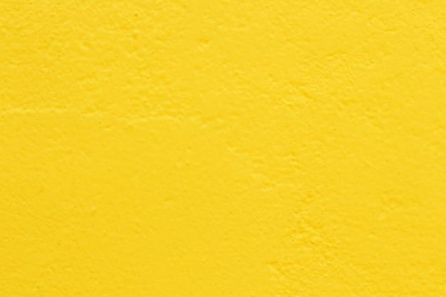 Jasnożółty kolor tekstury ścian betonowych dla tła i dzieła sztuki projektowania.