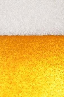 Jasnożółty piwny tło z pianą i bąblami