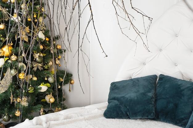 Jasny biały pokój z zielonymi poduszkami i baldachimem z gałęzi - świąteczna dekoracja w domu