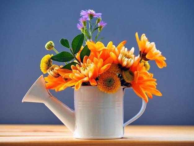 Jasny bukiet pomarańczowych chryzantem, stokrotek i fioletowych kwiatów w ogrodowej konewce