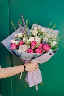 Jasny bukiet róż w ręku na zielonej powierzchni