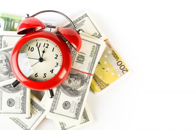 Jasny czerwony budzik w stylu retro na stos papierowych dolarów i euro.