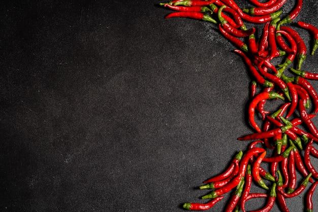 Jasny czerwony pieprz chili na szarym tle betonu. pikantne jedzenie, składniki.