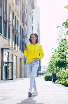 Jasny dzień. pełnowymiarowa pionowa piękna dziewczyna w żółtej bluzie z kapturem i okularach na ulicy, z białym smartwatchem na lewej ręce, patrząc na swój telefon.