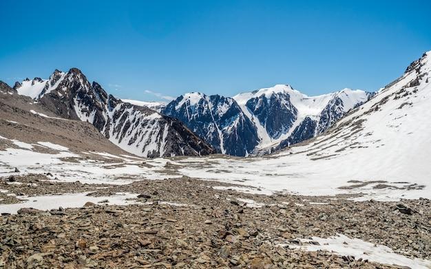 Jasny górski krajobraz z białym śniegiem na czarnych skałach. minimalistyczny charakter tła śnieżnego zbocza góry.