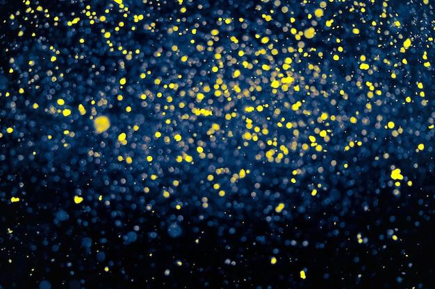 Jasny i ciemny żółty i niebieski rozmycie koło bokeh na czarnym tle dla swojego projektu.