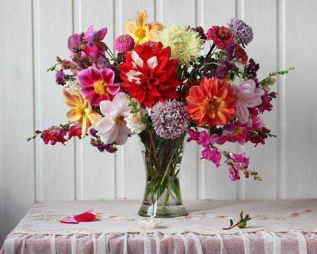 Jasny jesienny bukiet dalii i astry na stole w pobliżu białej ściany rustykalne kwiaty wewnętrzne w szklanym wazonie