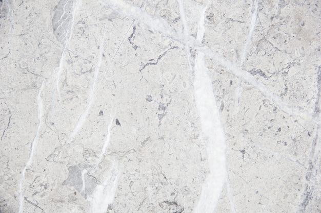 Jasny kamień naturalny z smugami. marmurowa tekstura. delikatny ciepły krem. kamienne tło