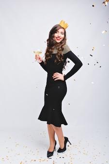 Jasny karnawał, przyjęcie noworoczne atrakcyjnej radosnej kobiety w luksusowej czarnej sukience na wysokich obcasach na białej przestrzeni