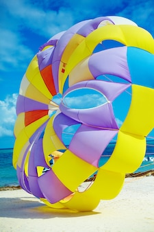 Jasny kolorowy rainbow parachute na plaży za błękitną oceaniczną wodą