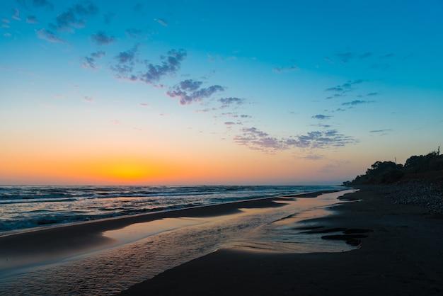 Jasny kolorowy wschód słońca nad brzegiem morza