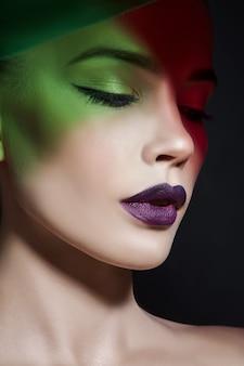 Jasny kontrastowy makijaż uroda portret kobiety w odcieniach niebieskiego i czerwonego cienia.