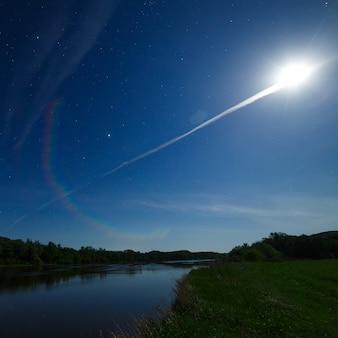 Jasny księżyc w pełni na rozgwieżdżonym nocnym niebie nad rzeką, lasem i polem