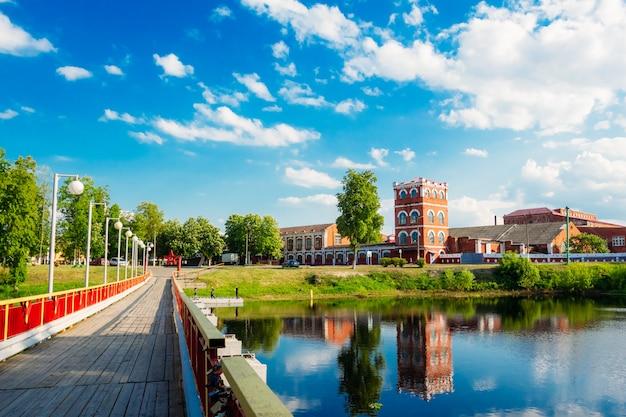 Jasny letni krajobraz z mostem na rzece i starą fabryką na brzegu