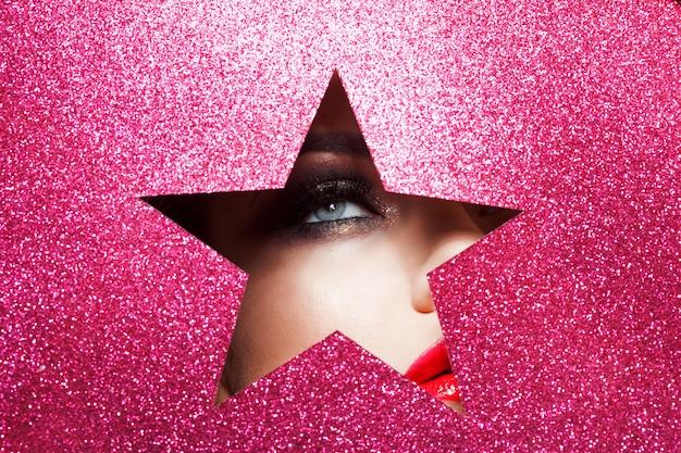 Jasny makijaż i jesteś gwiazdą. piękna dziewczyna z bliska, papier w kształcie gwiazdy.