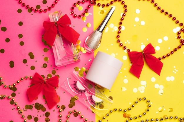 Jasny makijaż i układ perfum na pół różowym i pół żółtym tle