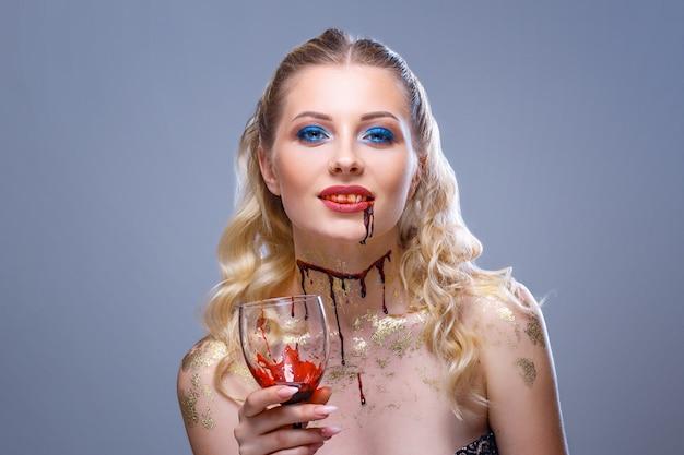 Jasny makijaż na twarzy pięknej kobiety trzymającej w dłoni kieliszek wina