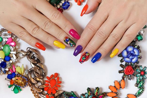 Jasny manicure na długich paznokciach z różnego rodzaju biżuterią wykonaną z koralików i cyrkonii.