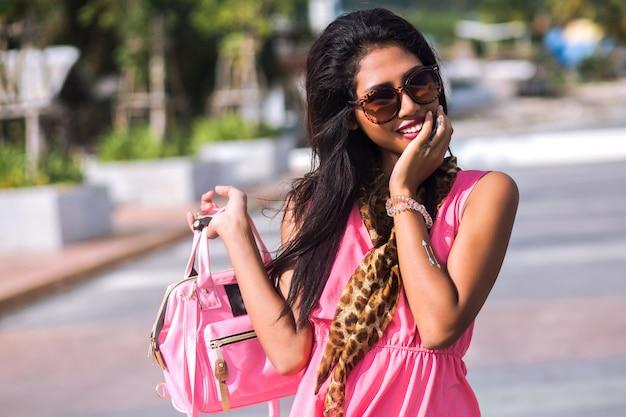 Jasny modny portret oszałamiającej zmysłowej brunetki azjatki tajki pozującej na santorini, ubranej w modny szalik w panterkę i okulary przeciwsłoneczne, jedwabnej mini różowej sukience, podróżującej samotnie.