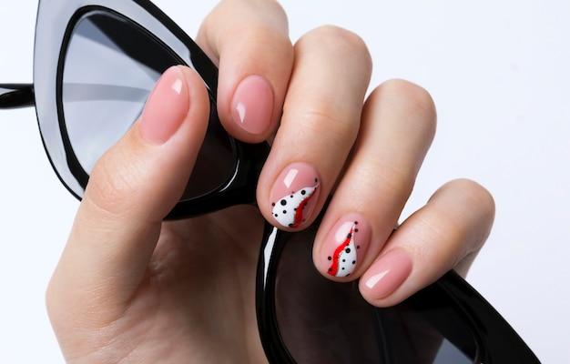 Jasny modny streszczenie manicure na kobiecej dłoni