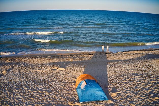 Jasny namiot nad morzem w wieczornym świetle. odpocznij na wybrzeżu