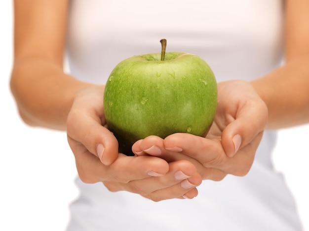 Jasny obraz kobiecych dłoni z zielonym jabłkiem