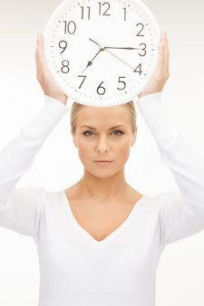 Jasny obraz kobiety trzymającej duży zegar