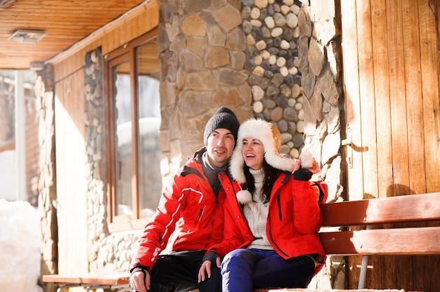 Jasny obraz pary rodziny w zimowe ubrania siedzącej na drewnianej ławce