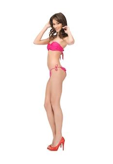 Jasny obraz pięknej kobiety w bikini i szpilkach