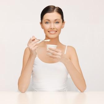 Jasny obraz pięknej kobiety z jogurtem