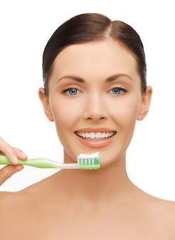 Jasny obraz pięknej kobiety ze szczoteczką do zębów
