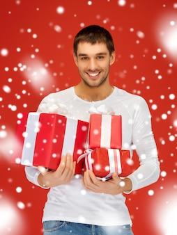 Jasny obraz przystojny mężczyzna posiadający wiele pudełek na prezenty.