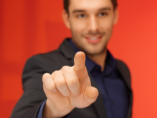 Jasny obraz przystojny mężczyzna w garniturze, naciskając przycisk wirtualny.