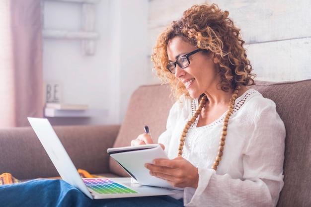 Jasny obraz światła okna dla kaukaskiej pięknej kobiety w średnim wieku pracującej w domu z laptopem i notebookiem. pisząc notatkę w książce długopisem jak w starym stylu, ale korzystaj z internetu na komputerze