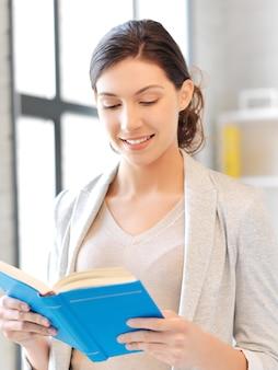 Jasny obraz szczęśliwej i uśmiechniętej kobiety z książką