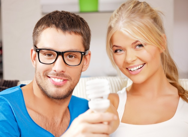 Jasny obraz szczęśliwej pary trzymającej energooszczędną żarówkę