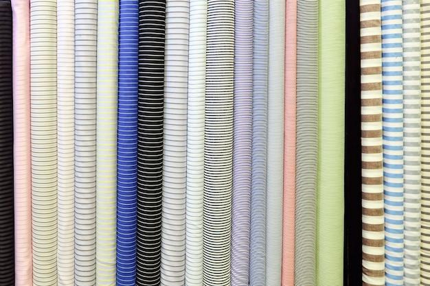 Jasny obraz tła. rolki z różnych pasiastych tkanin.