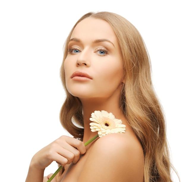 Jasny obraz uroczej kobiety z kwiatem gerbery.