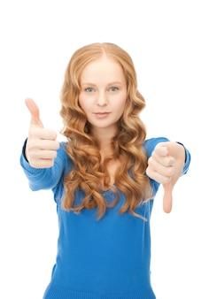 Jasny obraz uroczej nastolatki z kciukiem w górę i kciukiem w dół