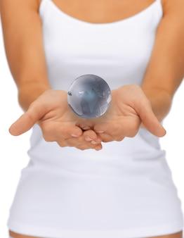 Jasny obraz zbliżenia kobiety trzymającej za ręce kulę ziemską