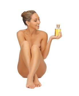 Jasny obraz zdrowej nagiej kobiety z butelką oleju