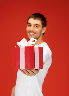 Jasny obrazek przystojnego mężczyzny z prezentem (skup się na pudełku)