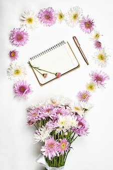 Jasny obszar roboczy bizneswoman. bukiet świeżych wiosennych kwiatów i notesów w pracy