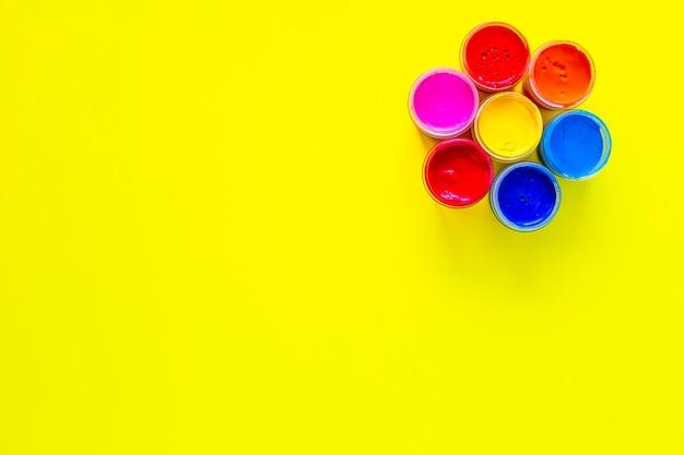 Jasny okrąg podobny do kwiatka złożony z puszek po farbie na żółtym tle z miejscem na...