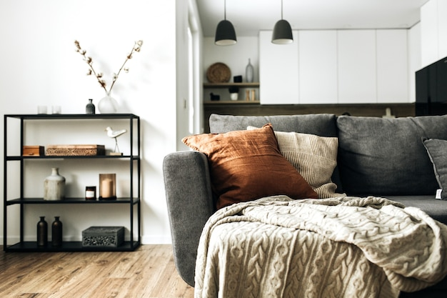 Jasny, otwarty salon z wygodną kanapą, dzianinową kratą, rudą poduszką, kuchnią, drewnianą podłogą.